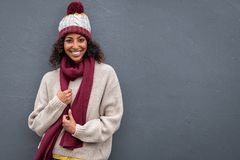 Happy black woman wearing warm clothes. Beautiful young black woman in winter clothing standing and leaning against grey wall. Portrait of attractive african royalty free stock images