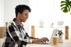 Happy black woman work at laptop having morning coffee. Happy African American female employee work at laptop in loft office, smiling black woman morning routine royalty free stock photography