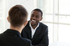 Happy black worker smiling having talk with colleague royalty free stock images