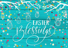 Happy Blessings Greeting holiday celebration card. With hand drawn lettering design, hanging eggs, tree branches and colorful scattered confetti on blue paint Royalty Free Stock Photography
