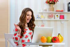 Happy blogger looking at laptop stock photos