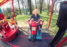 Happy blond baby girl in a carousel in Chindia Park Targoviste Romania. Carnival in Chindia Park Targoviste Romania Dambovita county Royalty Free Stock Images