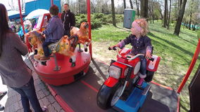 Happy blond baby girl in a carousel in Chindia Park Targoviste Romania stock video