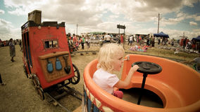 Happy blond baby girl in a carousel country fair in Romania Stock Images