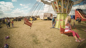 Happy blond baby girl in a chains carousel country fair in Romania Royalty Free Stock Images