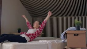 Happy Blond Beautiful Woman jumping On A Bed stock footage