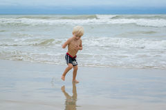 A happy blond boy child walking in water at a sea shore beach, Nha Trang, Vietnam royalty free stock images