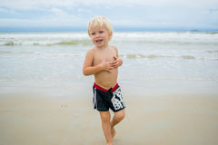 A happy blond boy child walking in water at a sea shore beach, Nha Trang, Vietnam stock image