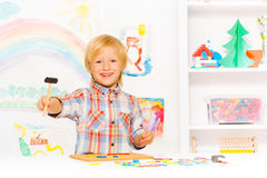 Happy blond boy with hammer and blocks in class Stock Photos