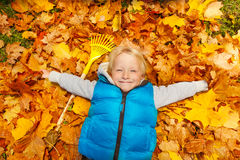 Happy blond boy laying on the autumn leaves Royalty Free Stock Photo