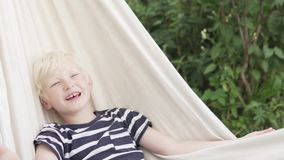 Happy blond boy lies in a hammock. And sings songs in the summer on a farm stock video
