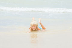 A happy blond boy lies in a water on a beach, Vietnam, Nha-trang royalty free stock photography