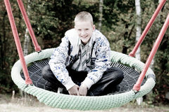 Happy blond boy in the swing Royalty Free Stock Photography