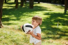 Happy blond boy wearing in the t shirt and beige shorts is standing on the lawn, holding football ball in his arms and royalty free stock images