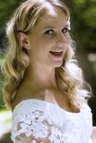 Happy blond bride. Portrait of happy young blond bride in white wedding dress; green nature background royalty free stock photo