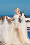 Happy blond bride in fashion wedding dress with blowing beige skirt Stock Photography