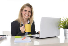 Happy blond business woman working on computer laptop with coffee cup Stock Images