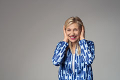 Happy Blond Businesswoman Covering her Ears royalty free stock images