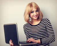Happy blond casual woman holding laptop in hand and toothy smili Royalty Free Stock Photography
