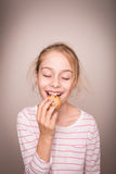 Happy blond caucasian child girl eating cookie. Stock Photos