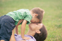 Happy blond caucasian kid outdoor family portrait at park kissed by his mum.  royalty free stock photos