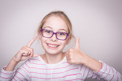 Happy blond child girl in glasses showing thumbs up gesture. Royalty Free Stock Photos