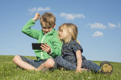 Happy blond children using smartphone (watching movie or playing game) sitting on the grass. Stock Photo