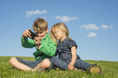 Happy blond children using smartphone (watching movie or playing game) sitting on the grass. royalty free stock photo