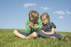 Happy blond children using smartphone (watching movie or playing game) sitting on the grass. stock photography