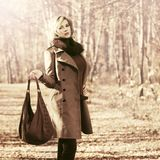 Happy blond fashion woman with handbag walking outdoor Royalty Free Stock Photography