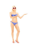 Happy blond female in bikini gesturing with her hand. Full length portrait of a happy blond female in bikini gesturing with her hand isolated on white background Royalty Free Stock Photography