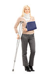 Happy blond female with broken arm holding a crutch posing Stock Photo