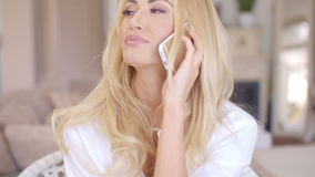 Happy Blond Female Calling at Phone Looking Left. Close up Happy Young Blond Female Calling at her Mobile Phone While Looking Left Frame. Captured at the Living stock video footage