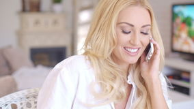 Happy Blond Female Calling at Phone Looking Left. Close up Happy Young Blond Female Calling at her Mobile Phone While Looking Left Frame. Captured at the Living stock footage