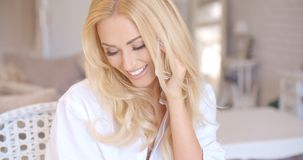 Happy Blond Female Calling at Phone Looking Left Royalty Free Stock Photography