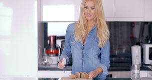 Happy Blond Female Chopping a Bread in the Kitchen stock video footage