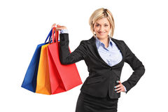 A happy blond female holding shopping bags. Isolated on white background Royalty Free Stock Images