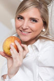 Happy blond girl with apple Royalty Free Stock Photography
