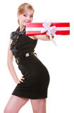 Happy blond girl in black dress holding red christmas gift box. Holiday. Royalty Free Stock Photo