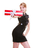 Happy blond girl in black dress holding red christmas gift box. Holiday. Stock Photos