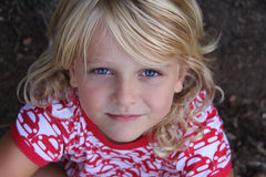 Happy blond girl with blue eyes. A blond girl with big blue eyes smiles up to the camera. Horizontal photo, positive emotions Royalty Free Stock Photo