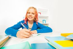 Happy blond girl with color hair do homework Royalty Free Stock Images