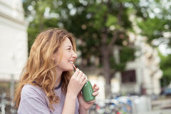 Happy Blond Girl Drinking a Bottle of Green Juice Royalty Free Stock Photography
