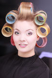 Happy blond girl hair curlers rollers by haidresser in beauty salon Stock Images