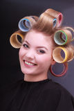 Happy blond girl hair curlers rollers by hairdresser in beauty salon Royalty Free Stock Photo