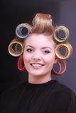 Happy blond girl hair curlers rollers by hairdresser in beauty salon Stock Images