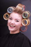 Happy blond girl hair curlers rollers by hairdresser in beauty salon Royalty Free Stock Image