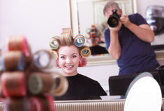 Happy blond girl hair curlers rollers in salon Stock Photography