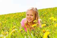 Happy blond girl in the meadow with flowers Stock Image