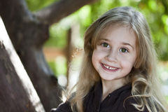Happy blond girl outdoors. Portrait of smiling blond haired girl outdoors Royalty Free Stock Images